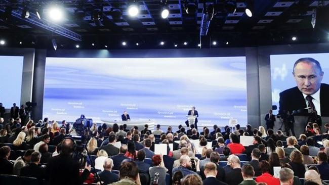 Photo of Putin speaking in front of  a conference